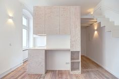 Pale wooden unit frames rooms and creates a new floor inside a Berlin micro-apartment