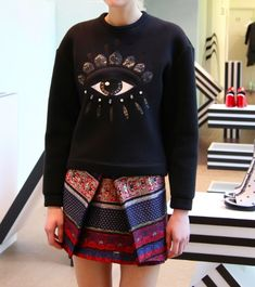 We love this Kenzo sweatshirt paired with a patterned skirt.