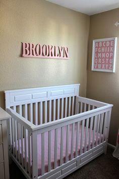 Baby Girl Nursery  www.themilehighmom.com    thinscolor brown for the walls with rose pink stripes and name in white