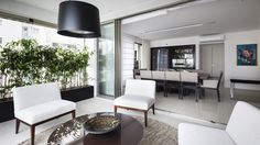Apartamento no Itaim com 345m² com uma ampla varanda de estar para receber os amigos. Na sala de jantar, foi projetado uma adega especialmente para o cliente que adora vinhos. Sobre a mesa, um rasgo com iluminação e escultura da galeria verbo.