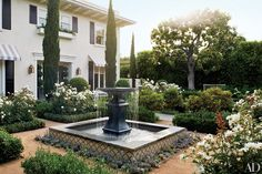 Devised by the Los Angeles landscape-design firm Modern Floristry, the Italianate garden in the entrance courtyard of this Beverly Hills home includes a pair of lead fountains from Authentic Provence.