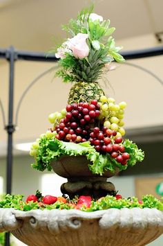 Fruit Display for Reception. I like the pineapple leaves as part of bouquet
