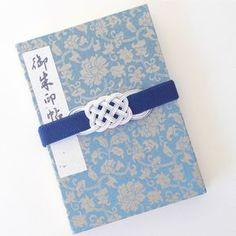 初詣などで神社を回る際に持ち歩きたい御朱印帳。バッグの中で開いてしまわないように留めておくゴムバンドも、水引飾りが気品を添えてくれます。