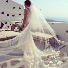 The bride looks ready for flight in her ethereal veil.