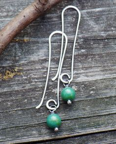 Blue Green Turquoise Sterling Silver Long Dangle Earrings Vibrant blue green 8mm turquoise stones are wrapped in sterling silver dangling from elongated dainty hand formed sterling hooks. The sterling has been oxidized for depth and color contrast. **pictures are taken in MACRO