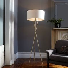 "Mid-Century Tripod Floor Lamp | West ElmMultipronged approach. The three intersecting legs of the Mid-Century Tripod Floor Lamp create an airy, sculptural base. Topped with a unique perforated light diffuser, it's a modern lamp that casts a soothing glow.   22""diam. x 66""h. Plated Antique Brass-finished base. Ivory-finished perforated cone diffuser. White linen shade. Imported."