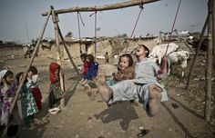 """portraitsofmiddleeast: """" An Afghan refugee boy and his sister enjoy a ride on an improvised swing, in a poor neighbourhood on the outskirts of Islamabad, Pakistan. Muhammed Muheisen/AP """" 2015 on POME Middle East Culture, Happy Eid Al Adha, Fotojournalismus, Pure Happiness, Poor Children, Poor Kids, Children Play, Kids Playing, Life Is Good"""