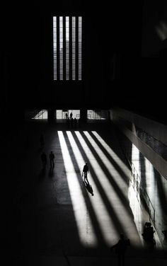 Visitors to Tate Modern walk through sunlight shining through the windows, in London