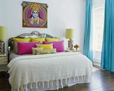 The master bedroom features a vintage mirrored headboard and a throw by Susan Chalom; the Vishnu needlepoint wall hanging is by Matthew Williamson for the Rug Company.