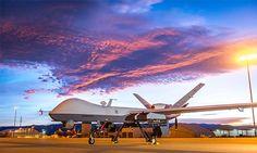 MQ-9 Reaper parked on a flightline below dramatic sunrise