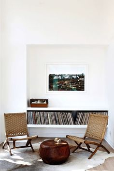white room with records on shelf and low woven chairs