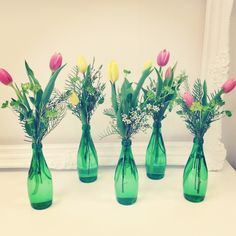 Fresh and Renewed - Flowers in Emerald Perrier Bottles- Cute for the outdoor deck tables!