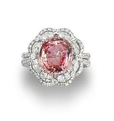 A padparadscha sapphire and diamond ring  Set with a cushion-cut padparadscha sapphire, weighing 5.23 carats, within an openwork double-tiered surround of marquise and round brilliant-cut diamonds, between diamond-set split shoulders, mounted in 18k white gold, the diamonds estimated to weigh approximately 1.40 carats in total by fomeyn