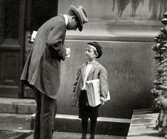 """June 1910. Philadelphia, Pa. """"Michael McNelis, 8 years old, a newsboy. This boy has just recovered from his second attack of pneumonia. Was found selling papers in a big rainstorm today."""" Photo by Lewis Wickes Hine."""