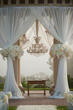 This alter is so beautiful! DIY Inspiration. Clasic metal alter with tulle or organza draped to the sides--met with flowers and crystals hanging above. Beautiful!!