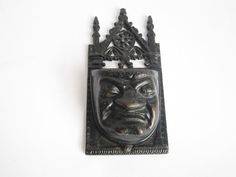 Antique cast iron match holder. Grumpy face match holder in the style of a high gothic gargoyle figure. This vintage wall hanging match holder was made in England in the style of the grotesques as see