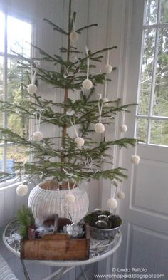 Christmas tree on the veranda decorated with white woolen bobbles Romppala - kotoilua ja puutarhanhoitoa