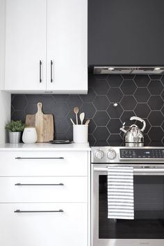 07 a minimalist white kitchen with a matte black hexagon tile backsplash, which is accented with white grout - DigsDigs Old Kitchen Tables, Kitchen Linens, Kitchen Decor, Black Backsplash, Kitchen Backsplash, Backsplash Ideas, Updated Kitchen, New Kitchen, Black Kitchens