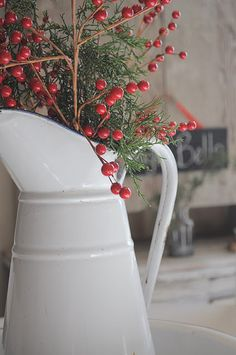 white pitcher with greens and red berries