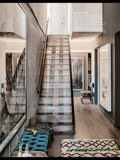 Living Etc., Oct 2014 Modern metal stairwell. Rough wood floors. Pop of color on bench. Large artwork.