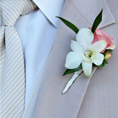 Kate and Patrick: The groom's boutonniere reflected the bride's bouquet colors and flowers with a white orchid, pink rose, and Hypericum berry. Image Credit: Tonya Malay Photography.