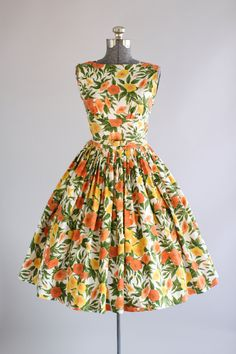 This vintage 1950s Jerry Gilden cotton dress features a gorgeous floral print in shades of yellow, orange and green. Shelf bust. Straps have