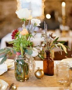 Mismatching Centerpieces Complementing a rustic barn venue, arrangements of eucalyptus leaves, carnations, lavender, and cotton blooms housed in various glass vessels, while gold painted pomegranates accented these reception tables.