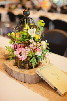 CENTERPIECE- tree stumps, flowers, and birdcage. Sensing a theme?