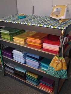 ironing board on top of shelves in a craft room. Love this idea