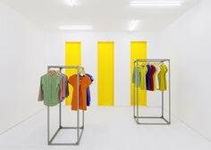Bright white surfaces, industrial shelving and a grey-veined marble counter create an uncluttered interior for this clothes shop by studio Fala Atelier