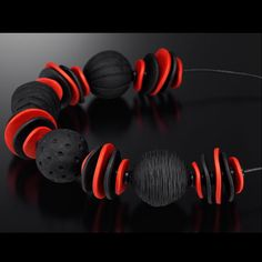 The subtlety of black paired with a vibrant red are a striking combination in this lightweight hollow textured polymer bead necklace.   The discs are draped fro
