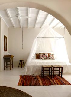 canopy bed, rugs, pillows, stools, arch, light, bohemian bedroom