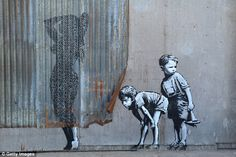 A stencil mural by Banksy depicting boys spying on a woman having a shower, as Banksy's Dismaland Bemusement Park opens to the public in Weston-Super-Mare, England