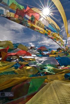 J. Marshall : Prayer flags flapping in the midday sun atop an outcrop at Namtso lake Tibet