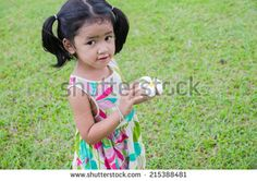 Portrait asian baby girl with flower in her hand - stock photo