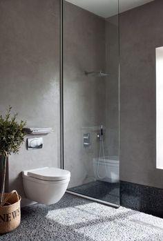 Rustige badkamer, licht grijs marmer stuc, grote zwarte glanzende tegels en glazen douchewand.