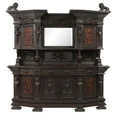 Monumental Continental Mahogany Cabinet late 19th century, in the Renaissance taste, the heavily molded and dentillated cornice surmounted by two side lion finials, over a recessed central mirrored section flanked to either side by canted cupboards, each inset with an elaborately pierced iron panel over fabric backing with a caryatid upright to either side, joined by a paneled and shield-carved back and scrolling uprights to a lower canted section fitted with three frieze drawers over two… Finials, Mahogany Cabinets, Carving, Wood Art, Cabinet, Furniture, Dark Wood, Beautiful Cabinet, Carved Furniture