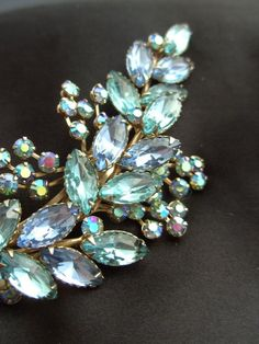 Pretty Vintage Brooch with light blue & green Rhinestone leaves, with small bluish green-gold luster rhinestone flowers!