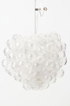 Bundeling clear ornaments to create a chandelier like this one with a single lightbulb in the center would throw light across the entire space and add a layer of sparkle and glamour to the ceiling.