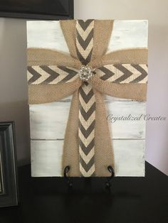This fabric cross is layered with burlap on the bottom and gray and white chevron on the top with a pretty rhinestone brooch embellishment in the center. Wood is hand painted to give a white weathered look. Can be hung on a wall or displayed on an accent Cross Wall Decor, Crosses Decor, Wood Crosses, Frame Crafts, Wood Crafts, Diy And Crafts, Picture Frame Wreath, Picture Frames, Burlap Cross