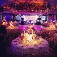"""Love LOVE the gorgeous uplighting and candles illuminating with the chairs and the place settings screaming """"Be our guest!""""  Ideal reception space would be outdoors on a beautiful night, but this space is stunning! The chandeliers! It really feels like you're walking into another world. Would like to add roses in the floral. And there must be a big dance floor! Oh yes, there will be plenty of dancing!"""