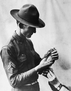 Attaching a message to a Signal Corps carrier pigeon. 1917-1918.