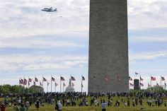 People gather at the base of the Washington Monument to watch as the U.S. space shuttle Discovery, on the back of a NASA 747 transport jet, flies over the National Mall on its way to its permanent display at the Smithsonian Institution, in Washington, April 17.