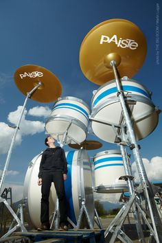 """The world's largest drumset """"THE BIG BOOM"""". The gigantic drumkit which measures 6.50m high and 8.00m wide (21x26 ft) was originally set up with all its parts – bass drum, snare, toms and cymbals.  Due to the massive specs of the drumkit, four drummers will team up to play it which makes this project rather difficult. The challenge will be especially difficult because each player has to synchronize their rhythmic patterns with one another while jumping around in 6m height."""