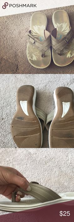 Clarks adjustable flip flops w/ memory foam! These flip flops feel like little clouds for your feet. The color is a perfect neutral beige to go with anything and the Velcro buckle detail is minimal but works perfectly to adjust them to make them fit looser or tighter across the top! Clarks Shoes Sandals