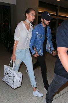 Gigi Hadid in a white shirt, light blue Sandrine Rose trousers, white Frasier Sterling choker, Goyard bag, and Kenneth Cole white sneakers.