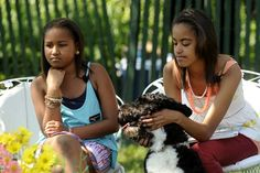 Malia Obama left and Sasha Obama pet their dog Bo while US President Barack Obama unseen reads 'Chicka Chicka Boom Boom' at the White House Easter...