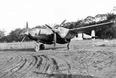 """A P-38 Lightning with the 80th Fighter Squadron, the """"Headhunters,"""" at rest at Dobodura, New Guinea, Dec 1943 – Feb 1944. Note the improvised wheel chocks."""