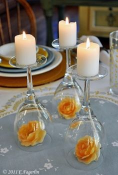 Easy and simple romantic centerpiece that will make her melt: turn three wine glassed inside down, a yellow rose bud inside each and finish up with medium size candles on top.
