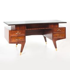 Italian rosewood desk, with brass in both faces and feet; green glass on the top; in the style of Gio Ponti